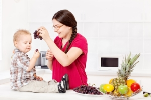 Mother Feeding Child In Kitche